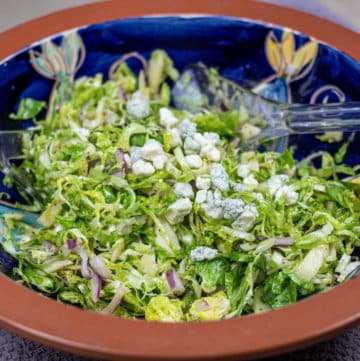 brussels sprouts coleslaw with blue cheese in a blue and brown bowl with salad tings
