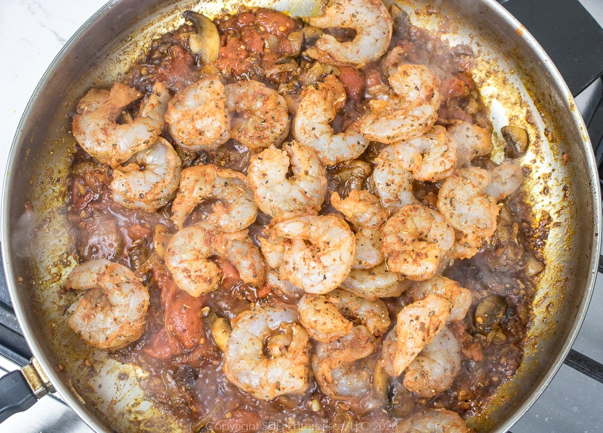 seasoned shrimp added to the mushroom, onions, tomatoes and spices in a frying pan