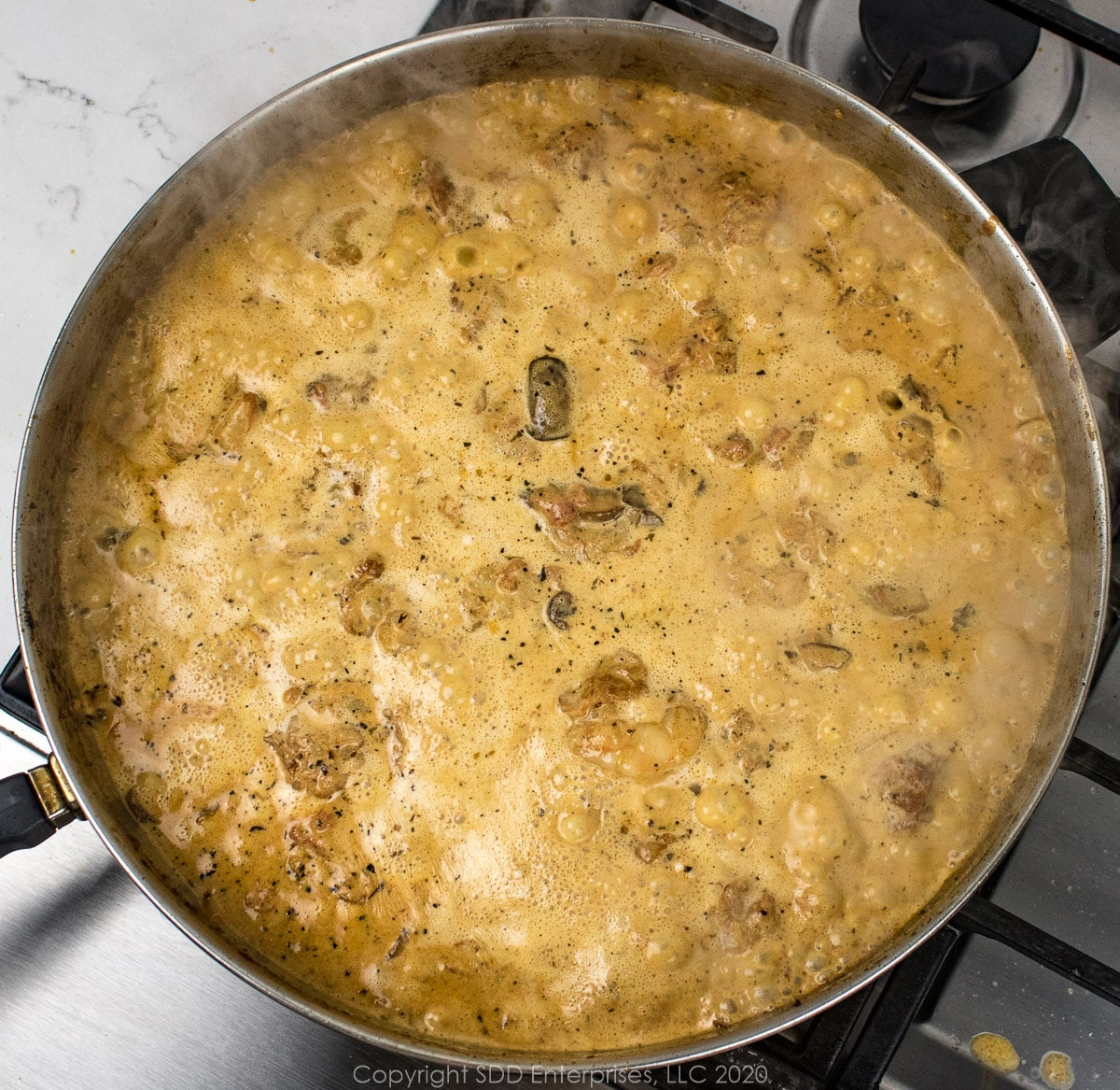 cream added to frying pan with mushroom, onions and tomatoes