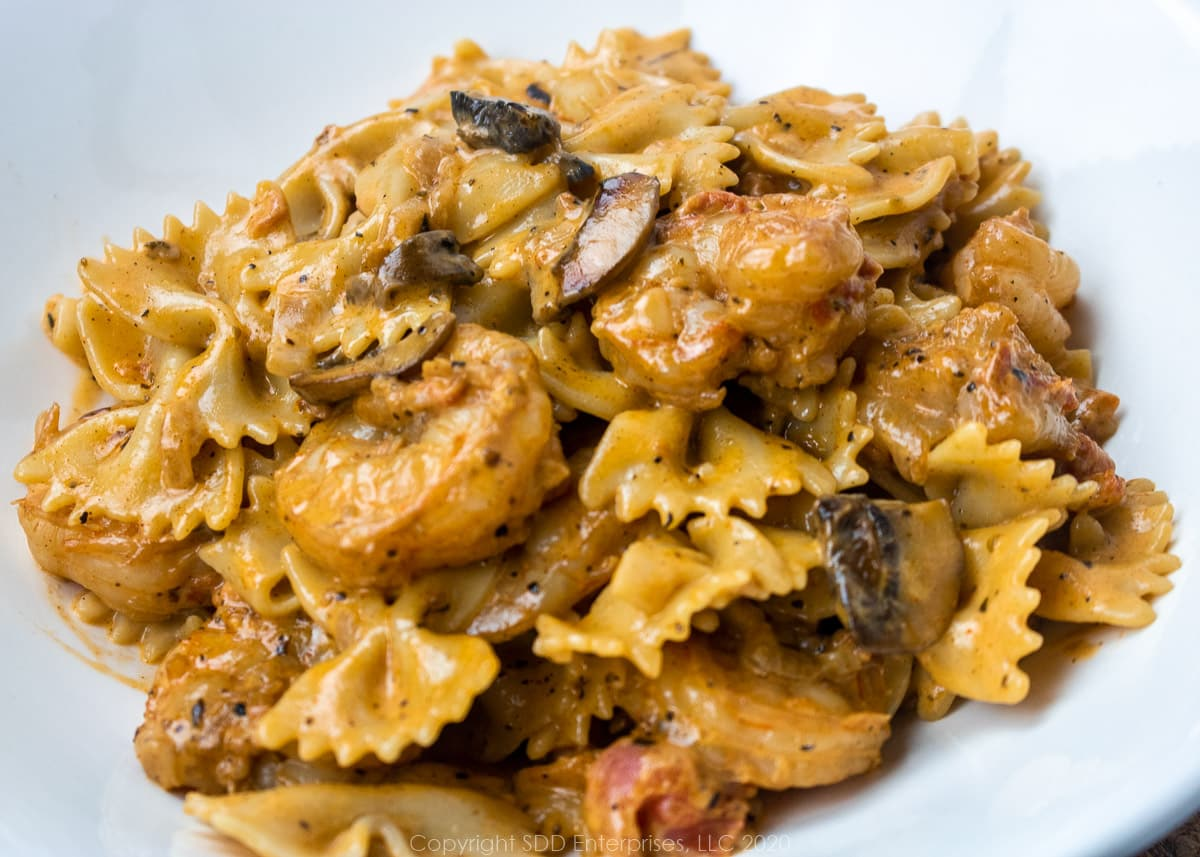 shrimp with pasta in a creamy mushroom sauce in a white bowl