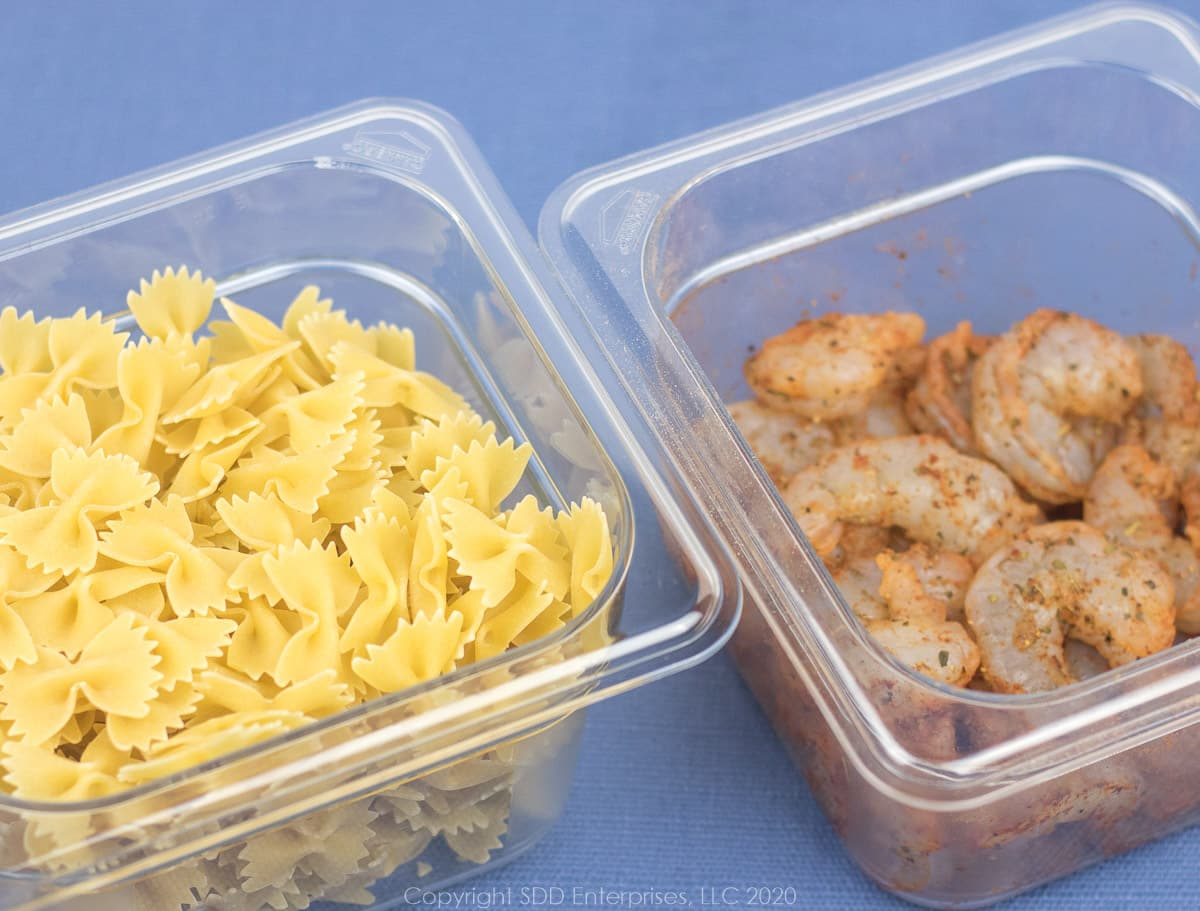 dry bowtie pasta and seasoned shrimp in bowls for creamy shrimp pasta