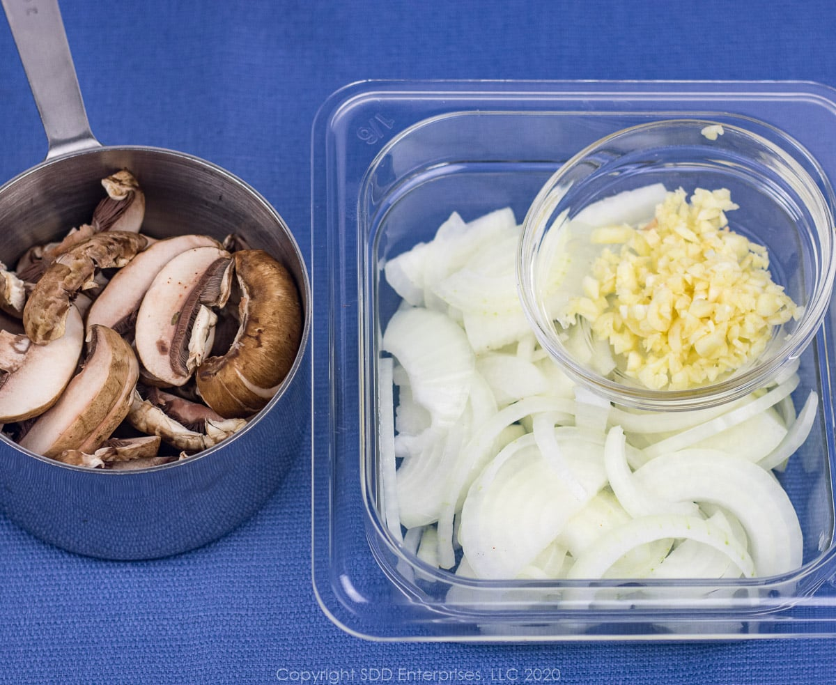 sliced mushroon, onions and chopped garlic in prep bowls