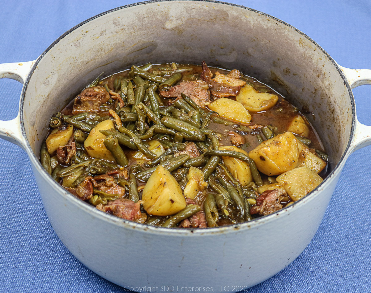 smothered green beans with potatoes and ham in a dutch oven