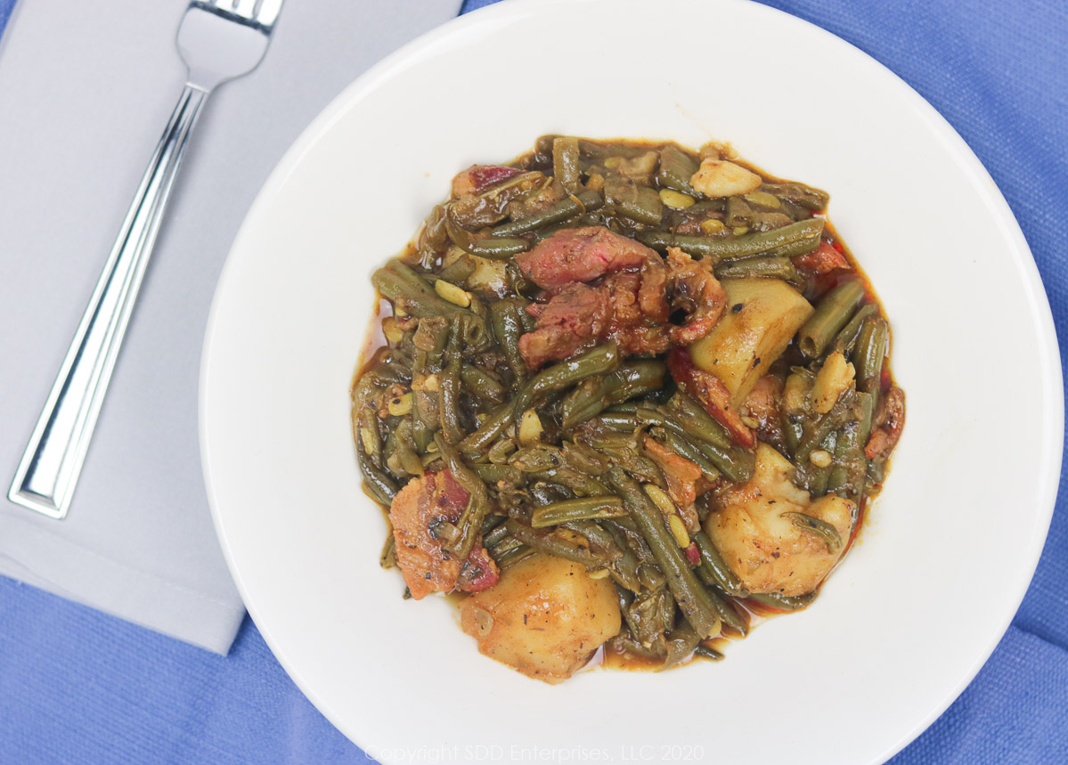 smothered green beans with potatoes in a white bowl with napkin and fork
