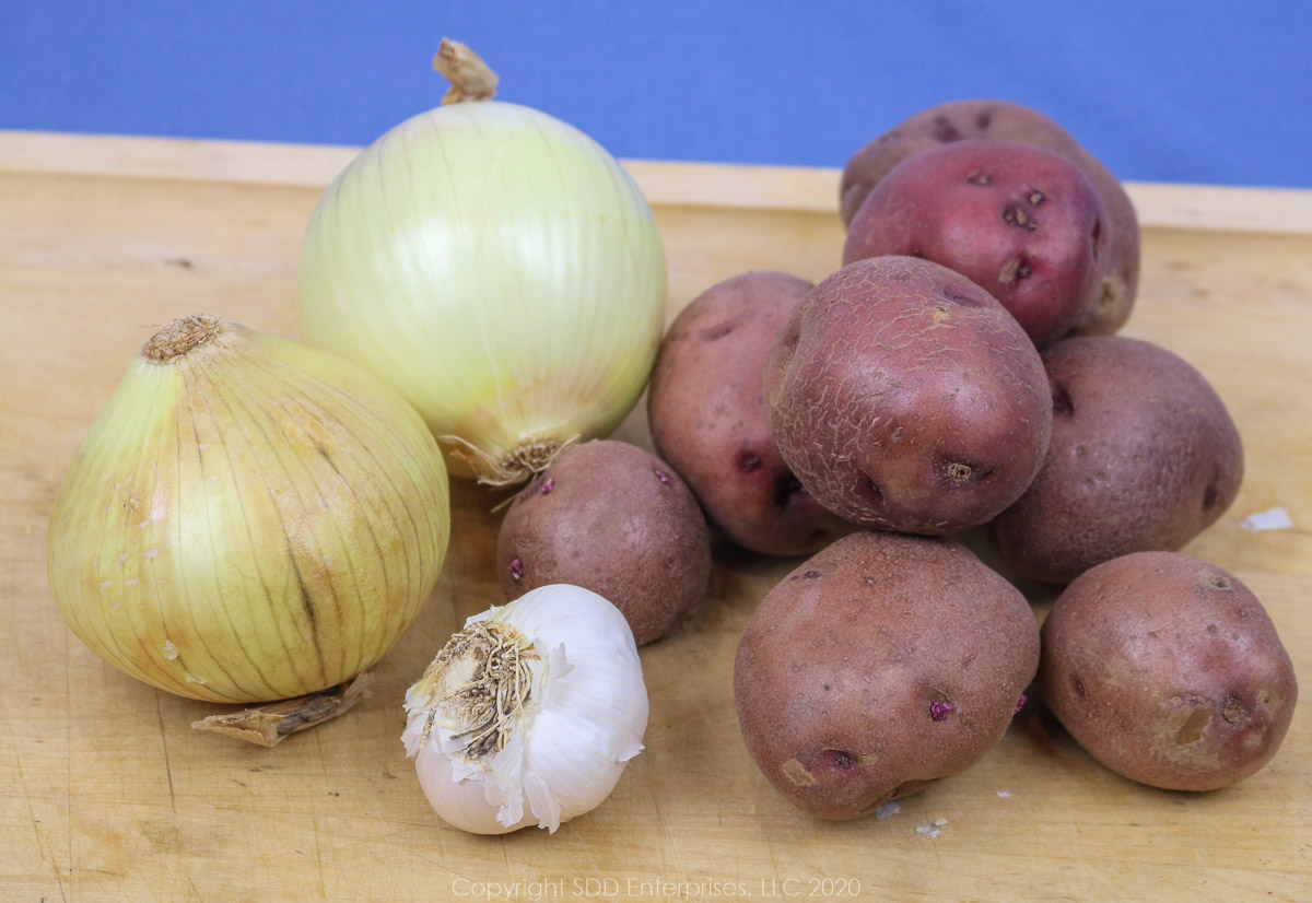 red potatoes, yellow onions and garlic pods on a cutting board