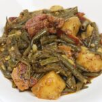 green beans smothered with potatoes, ham and bacon in a white bowl