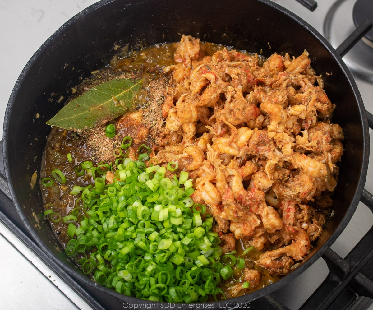 crawfish tails and green onions added to vegetables in a dutch oven for stuffed peppers