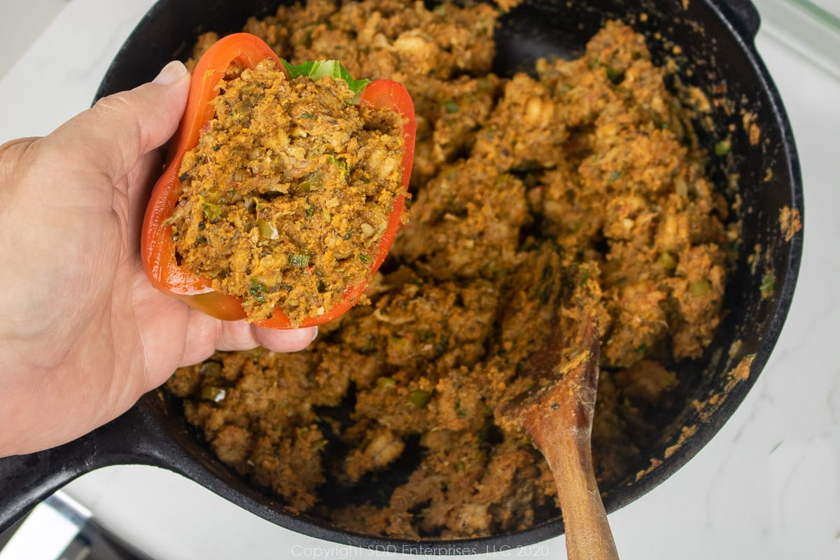 crawfish stuffing placed in a hlaf bell pepper over a dutch oven of stuffing