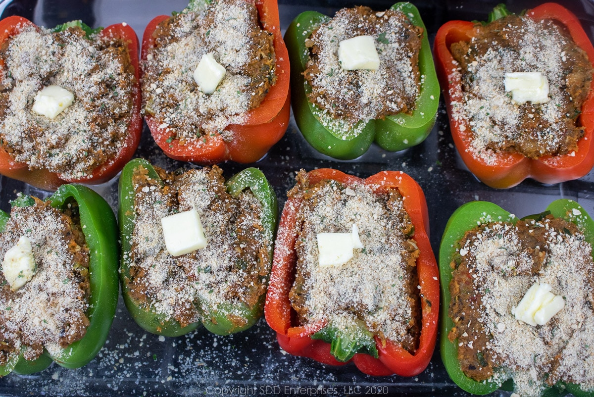 stuffed bell peppers with breadcrumbs and butter on top in a baking dish ready for the oven