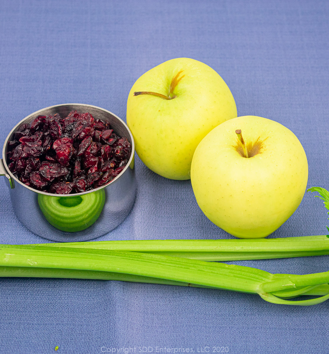 celery, two golden delicious apples and dried cranberries in a measuring cup