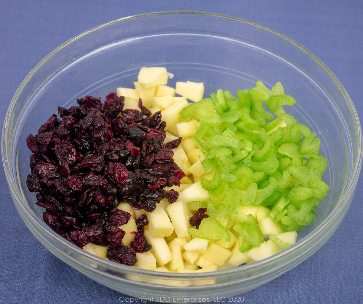dried cranberries, diced apples and sliced celery in a clear bowl