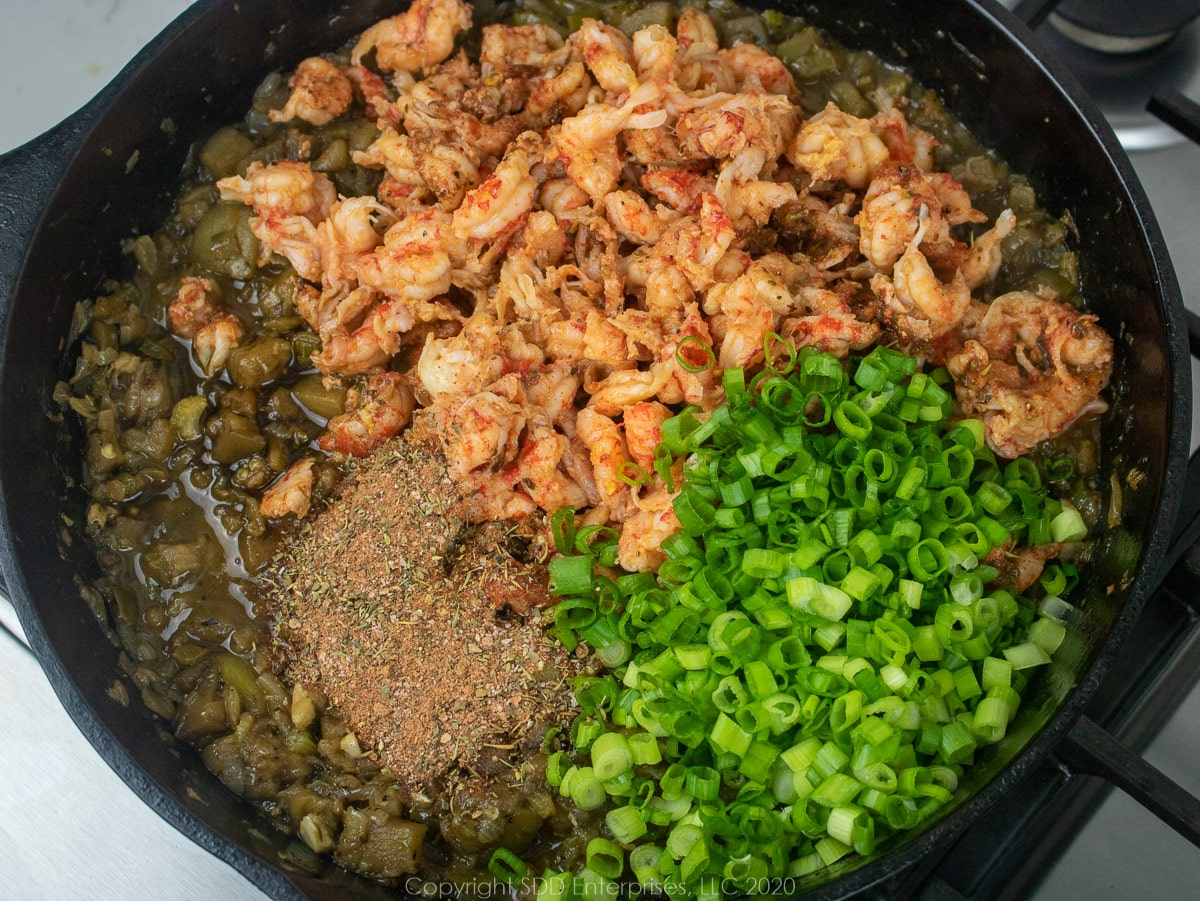 crawfish and green onions in a cast iron pan with sauteed vegetables