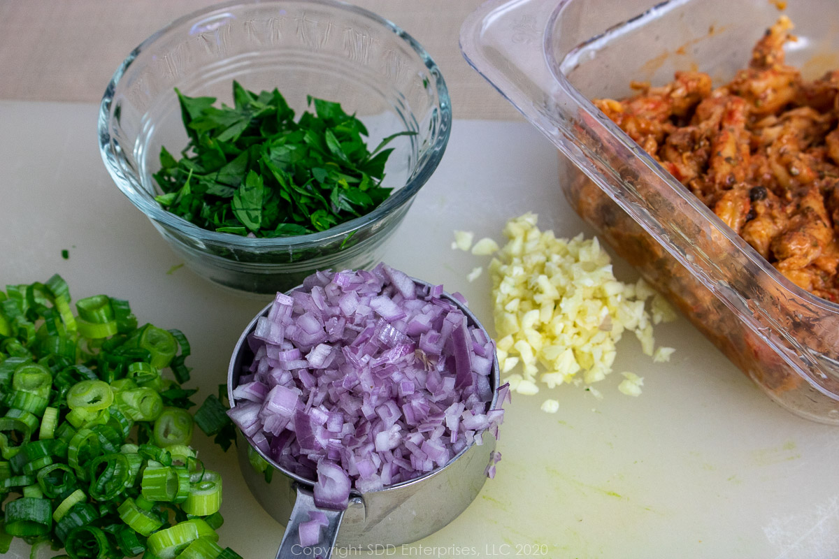 chopped green onions, shallots, garlic, parsley and crawfish tails for crawfish cream sauce