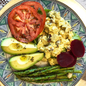 chicken salad, beets, asparagus, avacado and tomatoes on a plate with green trim