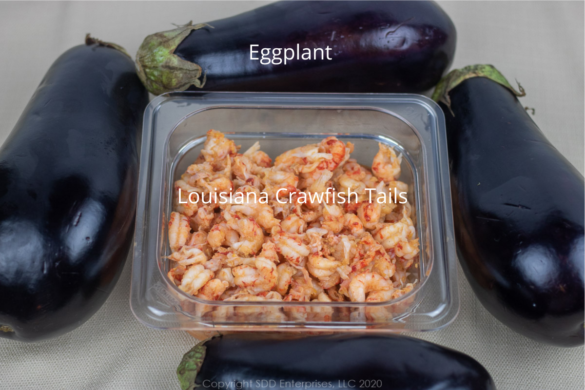crawfish tails in a prep bowl and four whole eggplants
