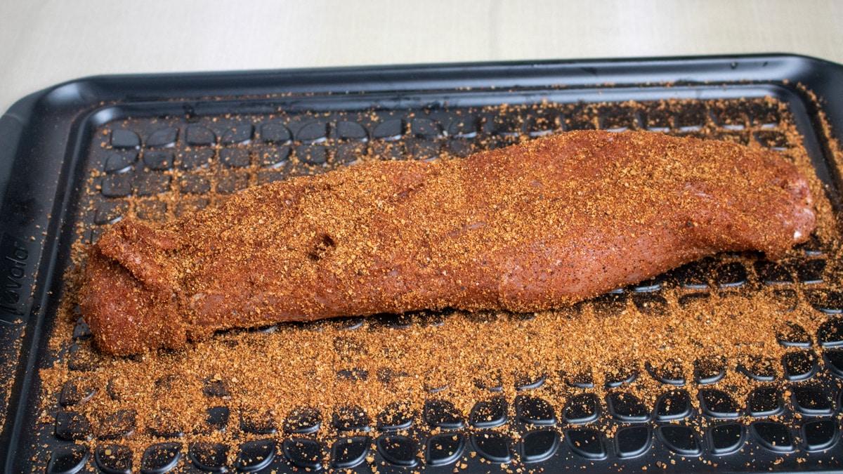 pork tenderloin resting in dry Cajun rub on a prep platter