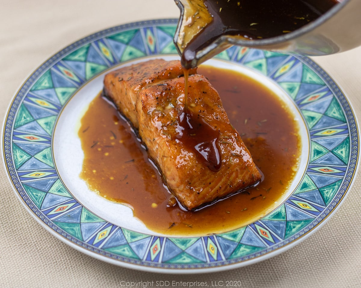 pouring cane syrup sauce onto a baked salmon fillet