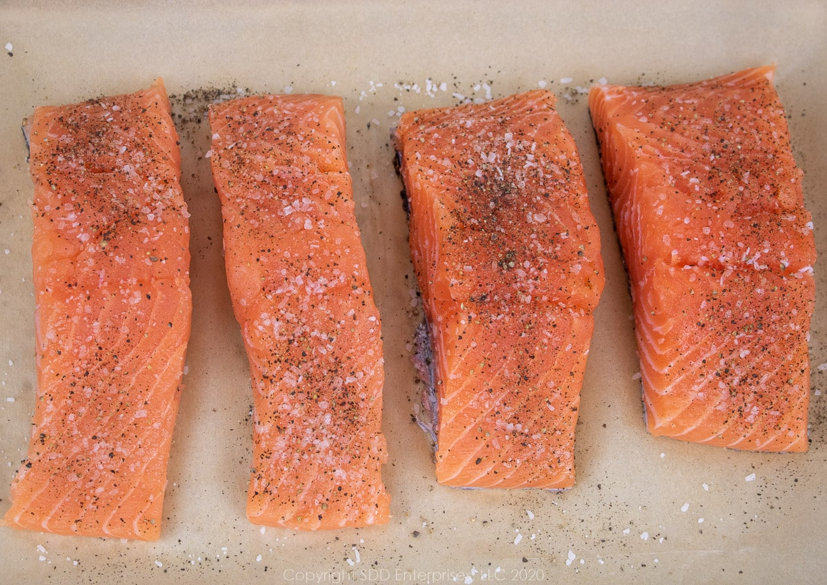 salmon fillets with kpsher salt and pepper on parchment