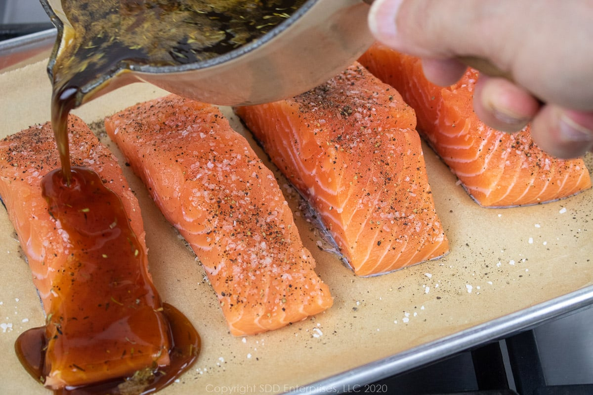 cane syrup sauce being poured over salmon filets on a baking sheet