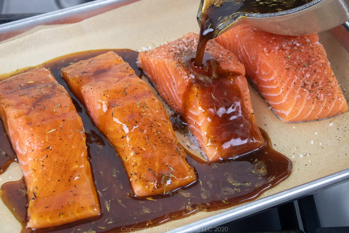 cane syrup sauce being poured over salmon fillets