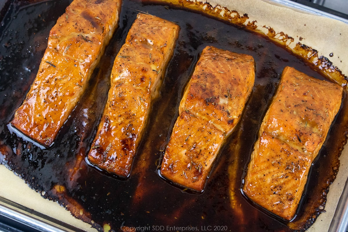 salmon fillets with cane syrup sauce on a baking sheet