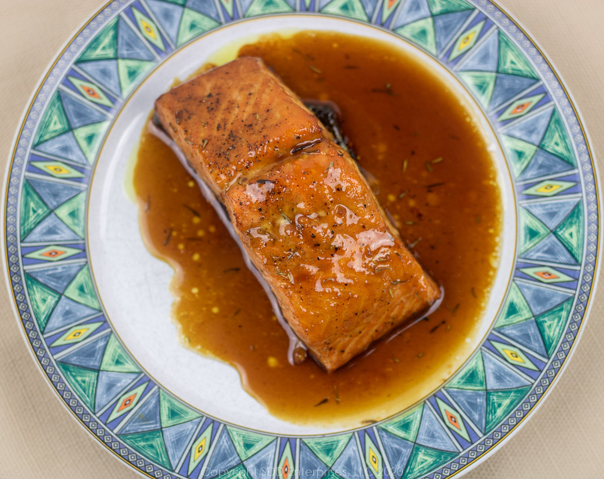 roasted salmon with cane syrup sauce on a white plate with blue-green trim