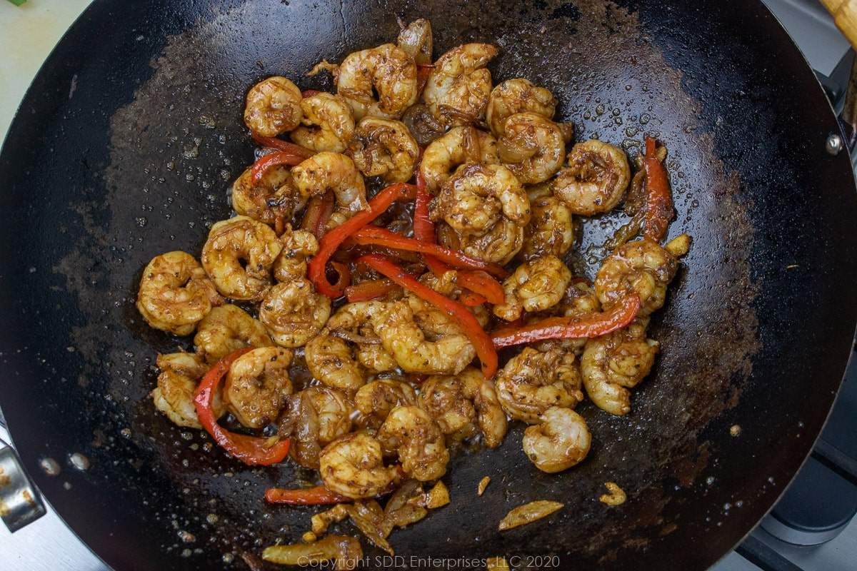 shrimp sauteing with onions and peppers in a wok