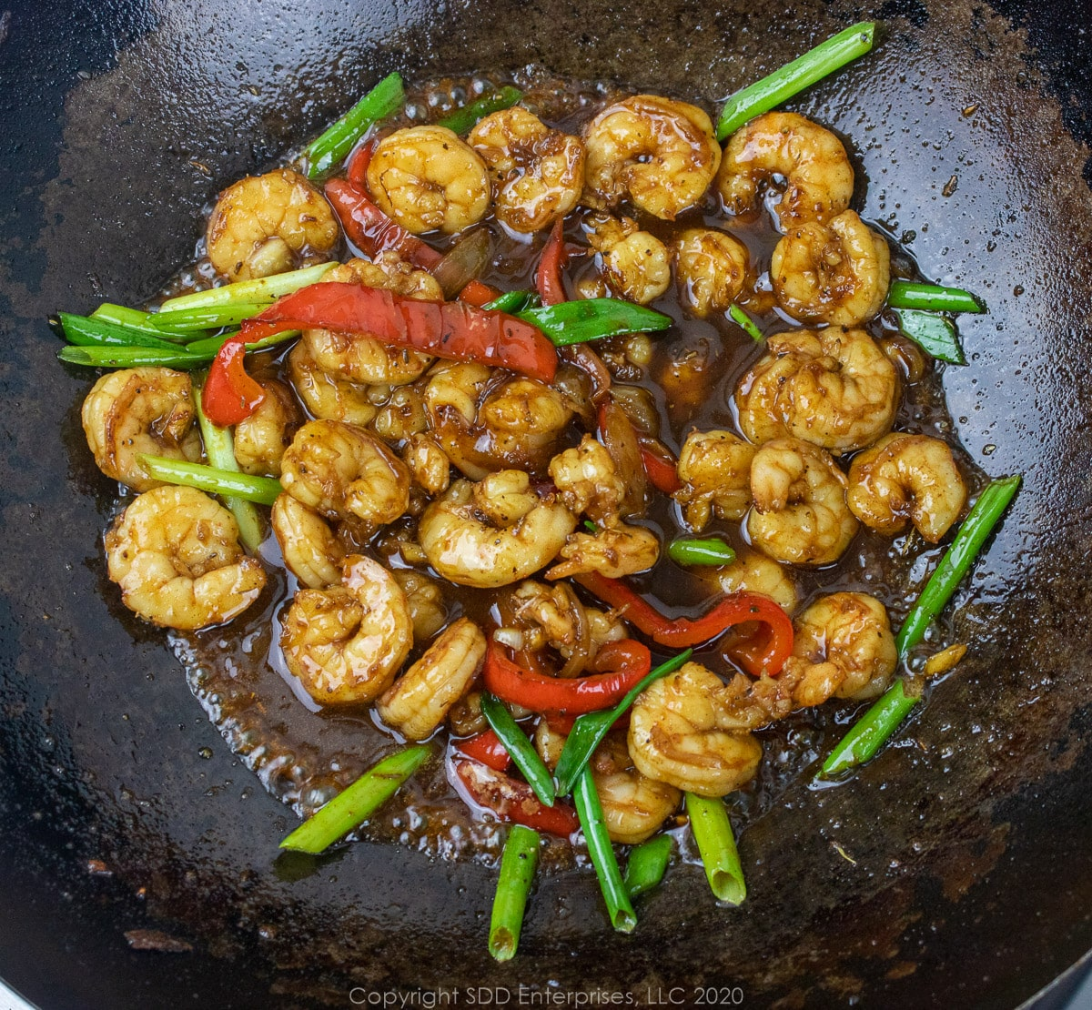 cane syrup sauce in the shrimp and onions and peppers in a wok