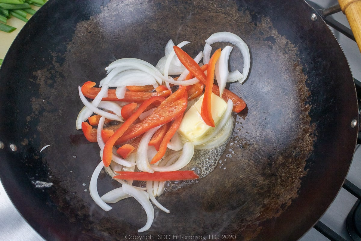 onions and peppers sauteeing in butter in a wok