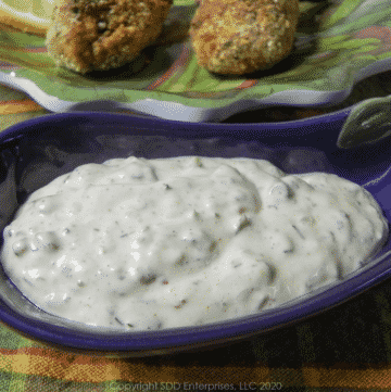 creole tartar sauce in a purple dish with stuffed shrimp on a green plate in the back ground