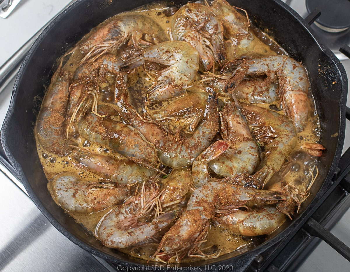 shrimp sauteeing in sauce in a cast iron skillet for barbecued shrimp