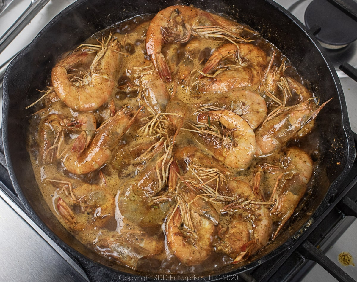 barbecued shrimp simmering in a cast iron skillet