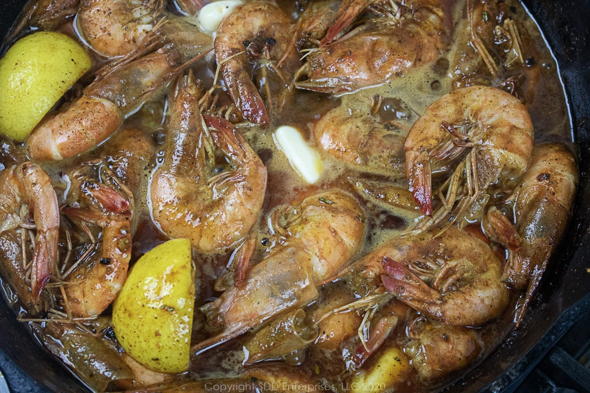 butter melting in barbecued shrimp in a cast iron skillet