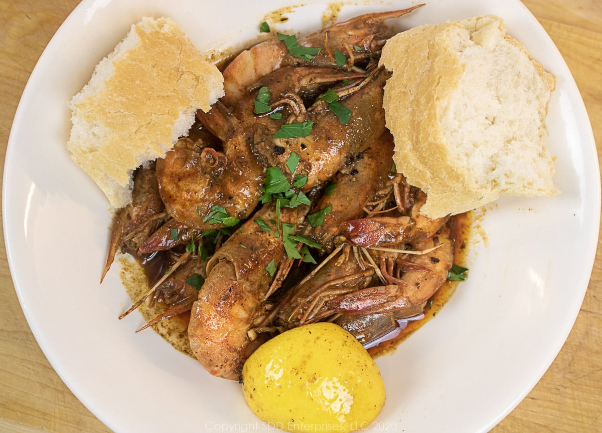 barbecued shrimp in a white bowls with lemon wedges and french bread