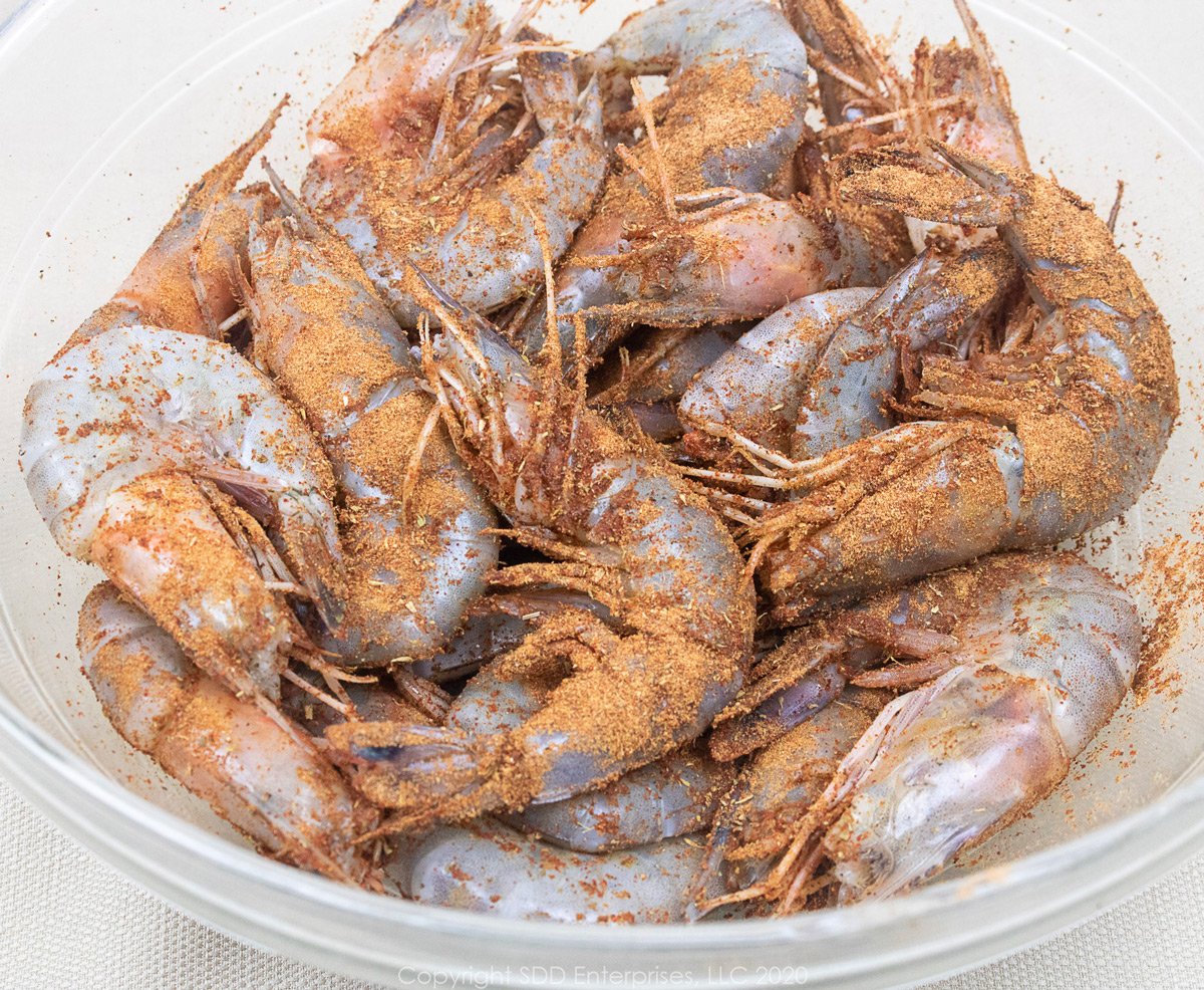 large shrimp in the shell with creole seasoning in a glass bowl