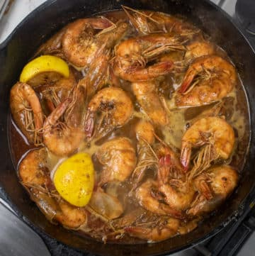 bbq shrimp in a cast iron skillet with lemon wedges