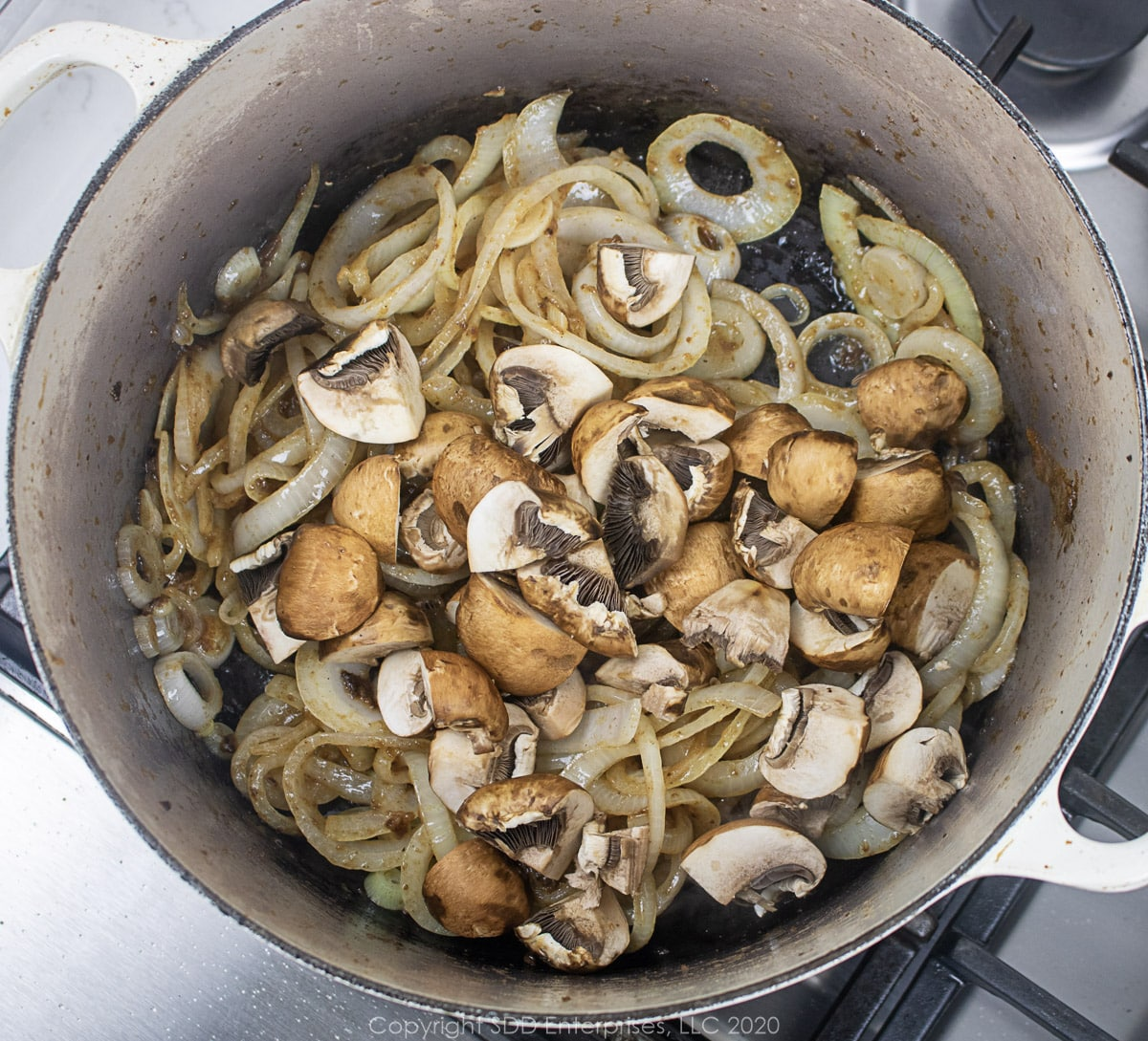 mushrooms and yellow onions frying in a dutch oven