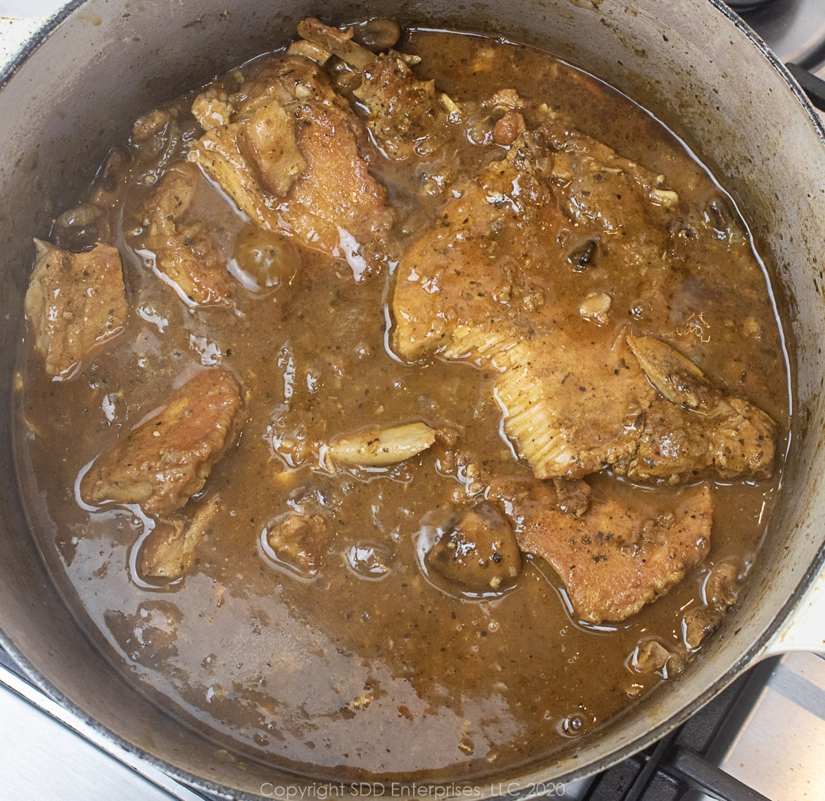 smothered pork chops simmering in gravy in a dutch oven