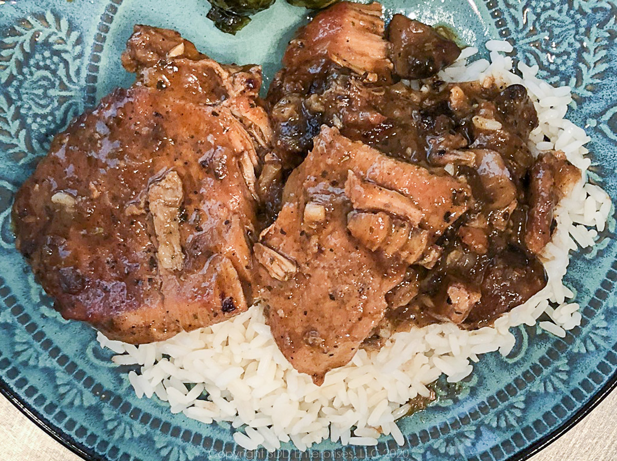 smothered pork chops served over rice on a lue-green plate