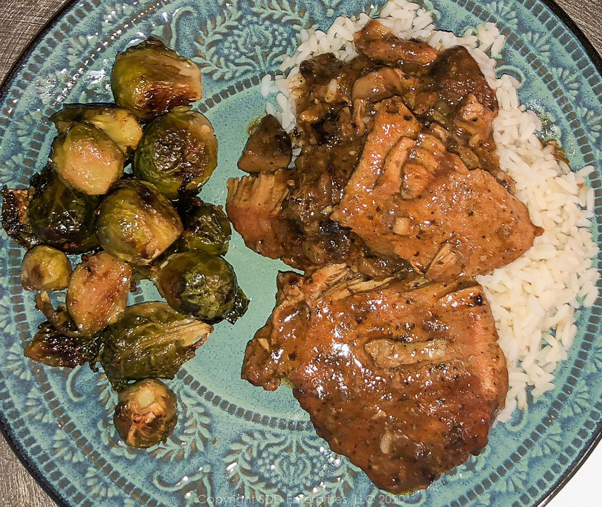 smothered pork chops with roasted brussels sprouts on a blue-green plate