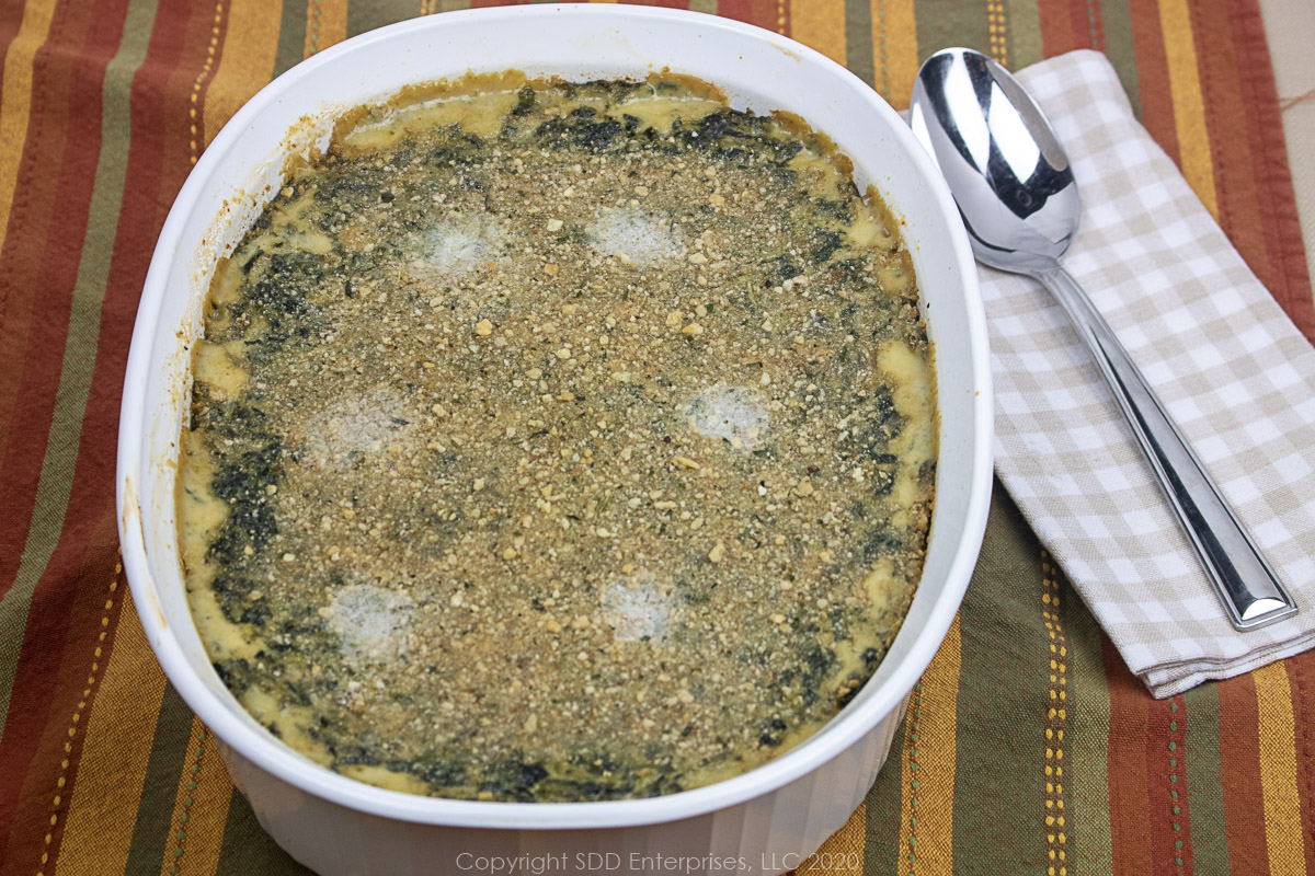 spinach madeleine in a white casserole dish with spoon on a napkin