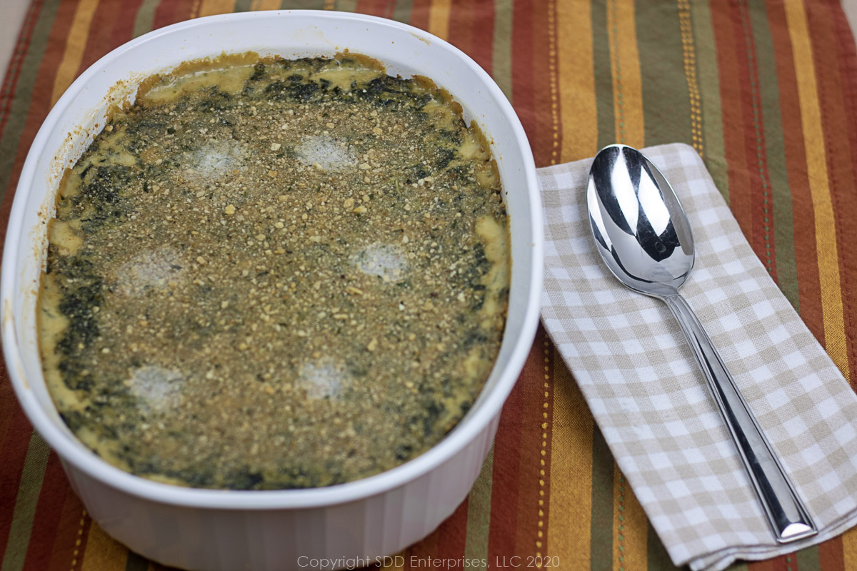 spinach Madeleine in a white casserole with a spoon on the side