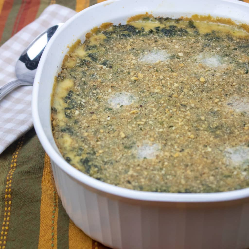 spinach madeleine in a white casserole dish with a spoon on the side