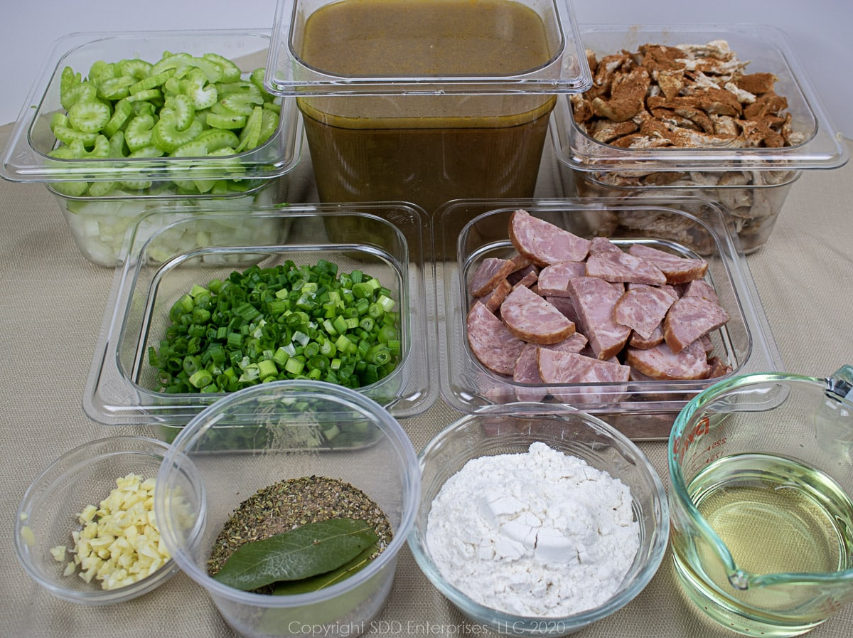 ingredients for chicken and andouille gumbo in individual prep dishes