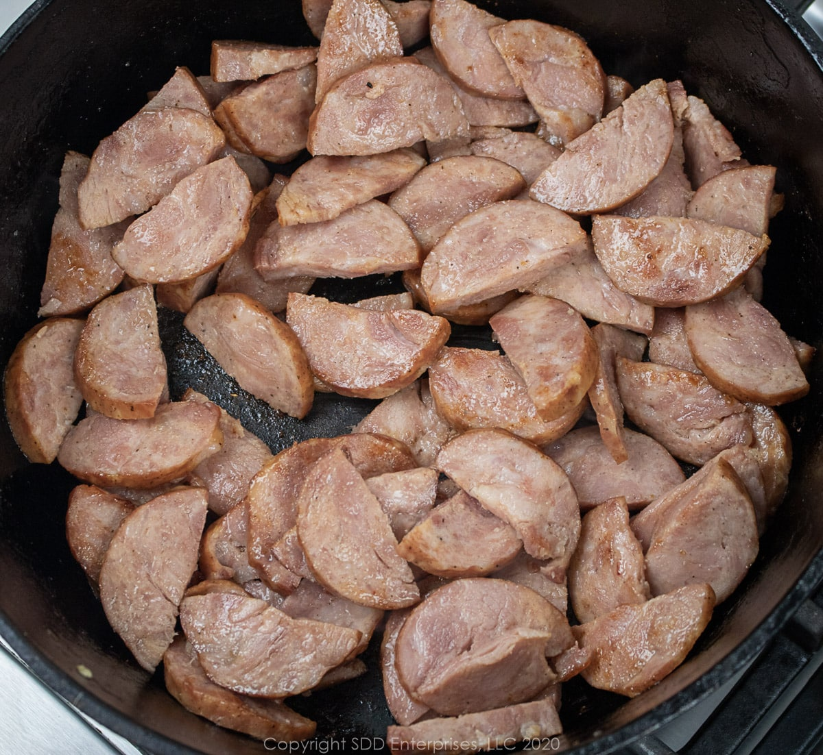andouille sausage frying in a dutch oven