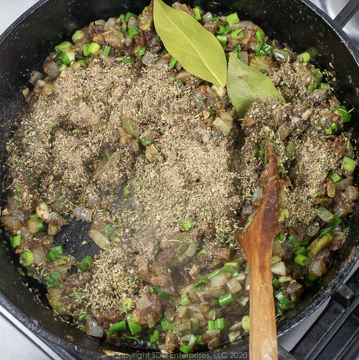 herbs and spices added to cooking roux and vegetables in a dutch oven