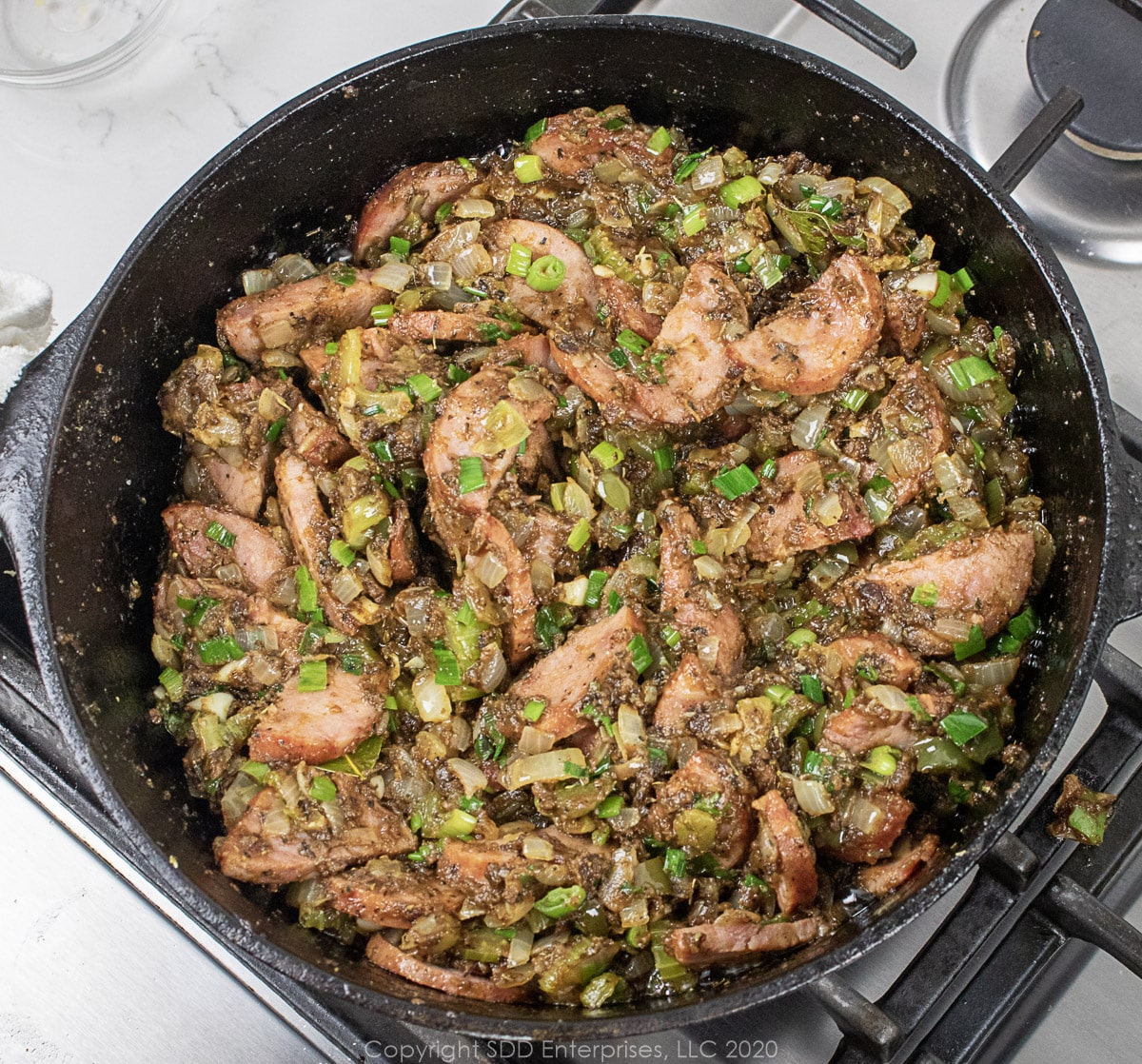sausage added to seasonings in a dutch oven