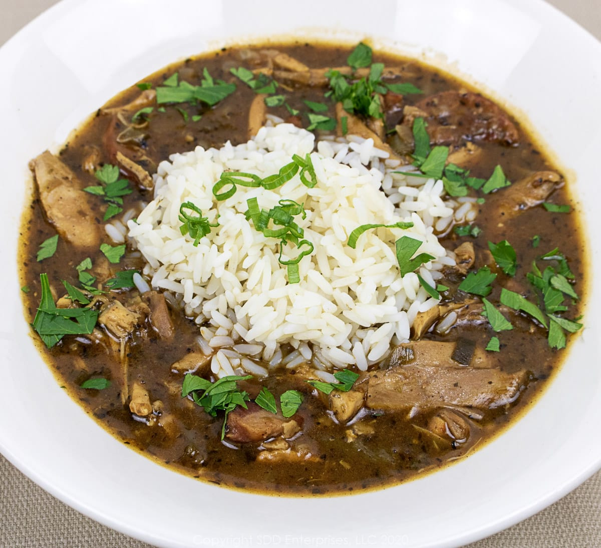 chicken andouille gumbo in a white bowl with garnish