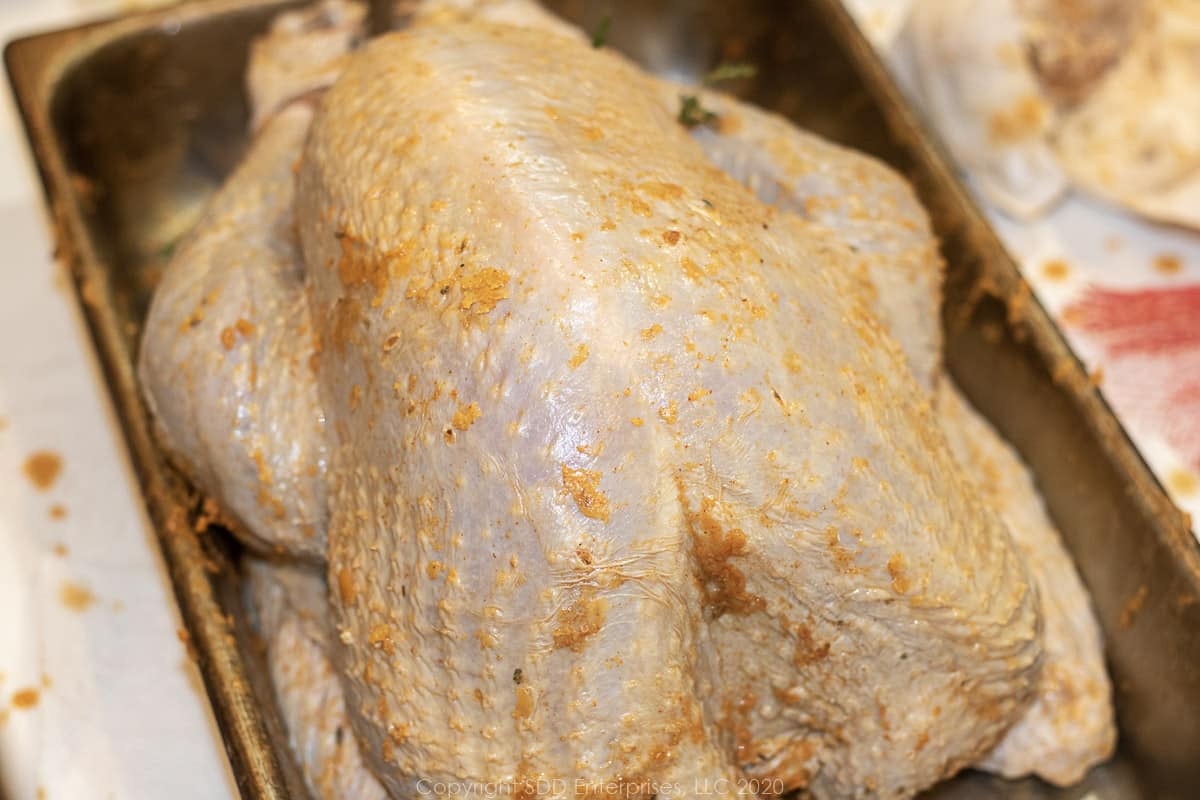 whole uncooked turkey with butter rub