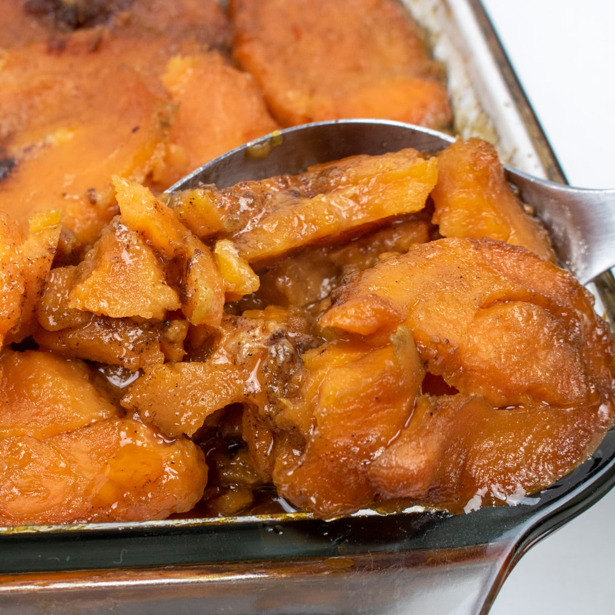 baked candied yams in a baking dish with a serving spoons